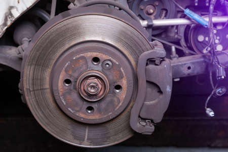 Photo pour Close-up metal disk in blue backlight - main element of brake system. Friction surface for brake pads. When braking, the pads are pressed against the disk and, due to the friction force, stop rotation - image libre de droit