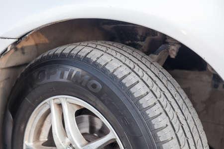 Photo pour Novosibirsk, Russia - 08.05.2020: Close-up of a used tire white car wheel on a dusty road disc. Seasonal wheel change in a car repair shop. - image libre de droit