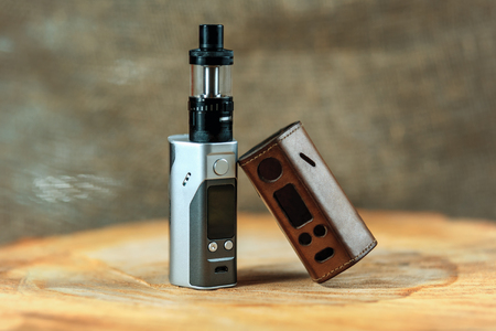 Vape. An electronic cigarette mod and leather case on a wooden table. Personal vaporizer.