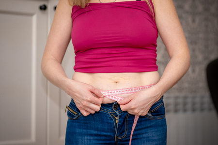 Photo pour Closeup of woman pinching belly fat. Young slim woman in blue shorts pinching her abdomen. Diet and weight loss concept. - image libre de droit