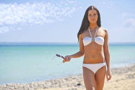 young woman on the sea in a white bikini
