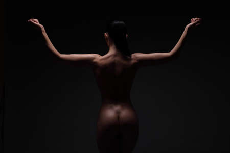 Photo pour nude young woman back and butts on a black background - image libre de droit