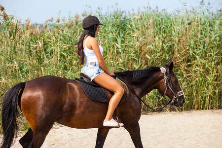 Photo pour young girl riding a horse on the beach - image libre de droit