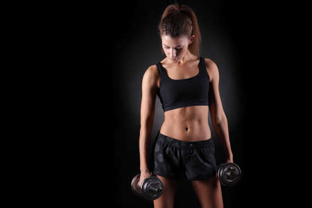 Photo for Beautiful fitness woman lifting dumbbells on a black background - Royalty Free Image