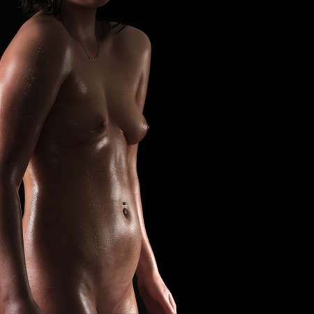 Photo for Beautiful oiled female body on dark background - Royalty Free Image