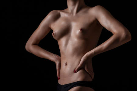 Foto de Nude body of the beautiful girl over dark background - Imagen libre de derechos