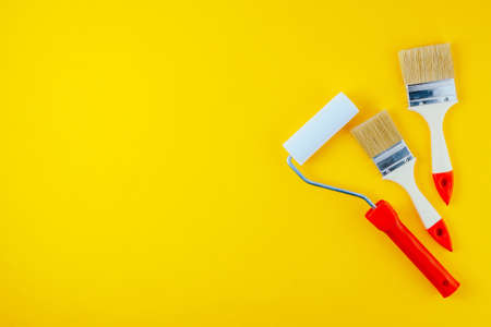 Paint brushes and roller on a yellow background. Space for text or design
