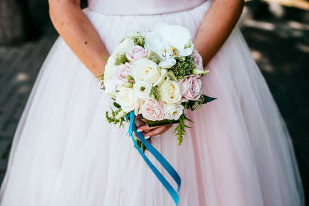 Foto für Bridal bouquet, hold the wedding bouquet in your hand, satin ribbons adorn the wedding bouquet of roses, on the background of the brides dress, fresh flowers, made by a florist - Lizenzfreies Bild