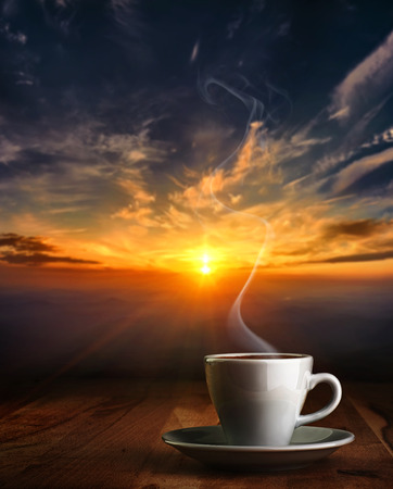 Coffee in white pottery cup on old wooden table with blurred image of  sunset or sunrise
