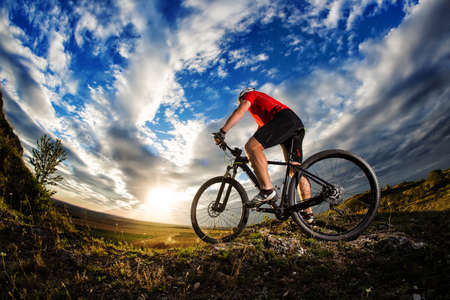 Man in helmet and glasses stay on the bicycle under sky with clouds.の写真素材