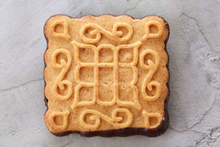 Square biscuits arranged in pattern on light textured background, close-up, shallow depth of field, selective focus.