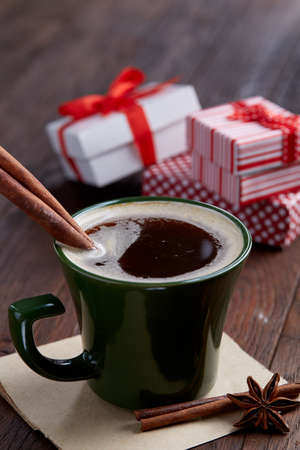 Still life with cup of coffee holiday gift in small red color box with pattern, covered with red ribbon and bow on rustic wooden background, top view, close-up, shallow depth of field, selective focus. Christmas background. Festive concept.