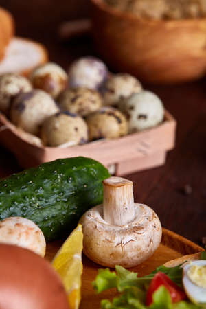 Fresh eggs of a quail with greens and vegetables on wooden table, selective focus, close-up, shallow depth of field. Composition of quail eggs, cherry tomatoes, cucumbers, mushrooms and spicies. Healthy food concept.