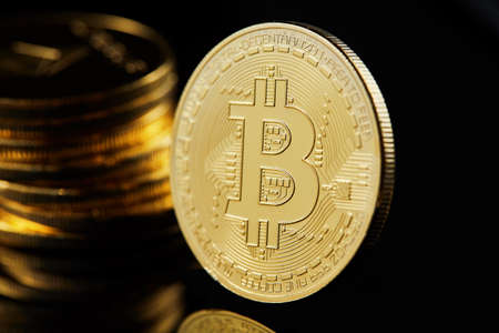 Conceptual image of crypto currency with isolated bitcoins on dark table. Focus of coins. Other in gradient blur.
