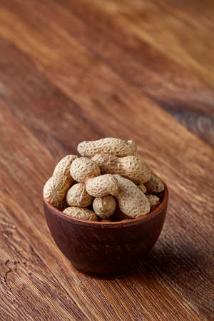 Unpeeled peanuts in wooden bowl over rustic wooden background closeup, selective focus. Some copy space for your text. Healthful and nutritious snack. Delicious ingredient for your every day cooking. Healthy lifestyle concept.