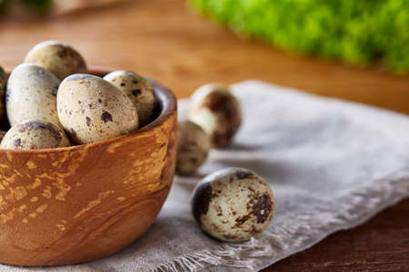 Preparation for making healthy salad with quail eggs, top view, close-up, selective focus. Delicious composition of fresh lettuce on cutting board and nutritious quail eggs in different bowls. Healthy food concept. Organic gastronomy.