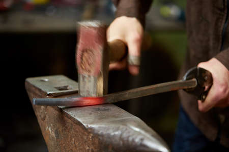 Close-up of a blacksmith's hands manipulating a metal piece above his forge in the smithy, selective focus. Blacksmith forges a red-hot iron in the forge. Blur pavement in background. Ancient manufacturing. Art and crafts concept.