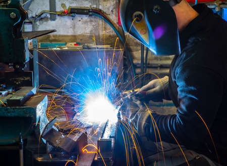 Photo pour Electric welding process. Worker in welding mask. Yellow sparks fly to the sides. Bright white. - image libre de droit