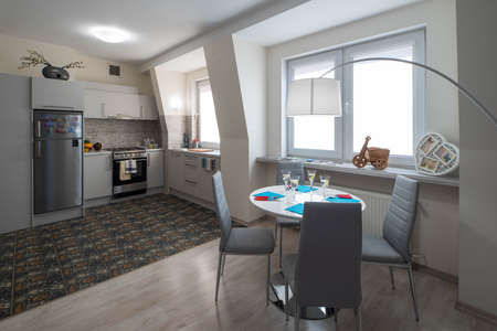 Photo pour Light interior of kitchen in studio apartment. Kitchen set. Table and chairs. Wall with windows. - image libre de droit