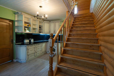 Photo pour Kitchen in private house. Staircase to the second floor. Modern wooden interior. Kitchen set and home appliances. - image libre de droit