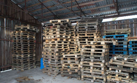Photo for Wooden pallets stacked on top of each other inside the warehouse. Wooden walls. - Royalty Free Image