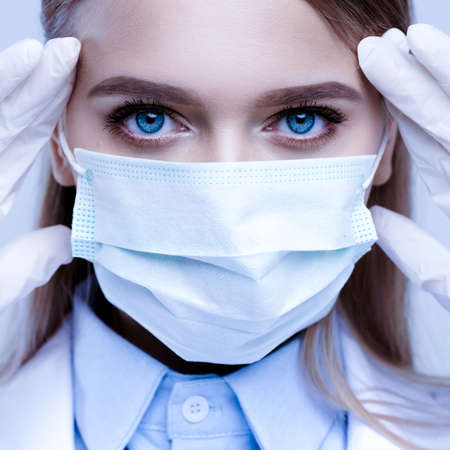 Photo pour Close-up portrait of female doctor in mask and medical gloves. Nurse touches the mask - image libre de droit