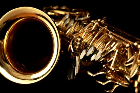 close up gold alto saxophone on black background