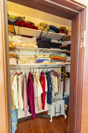 Photo for Storage room in the cottage with shelves and hangers, where different clothes hang and lie-t-shirts, shirts, pants, underwear. - Royalty Free Image