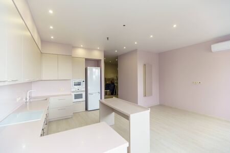 Foto de A large room with pink walls and a white kitchen set. Kitchen furniture is new with all kitchen appliances. In front of the kitchen is a white table. Fresh, new renovation.. - Imagen libre de derechos