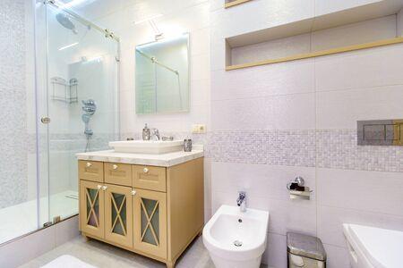 Foto de bathroom with elegant rectangular washbasin, toilet and shower. Mirror with light on top. The white tile.. - Imagen libre de derechos