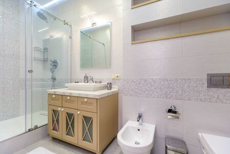Photo pour bathroom with elegant rectangular washbasin, toilet and shower. Mirror with light on top. The white tile.. - image libre de droit