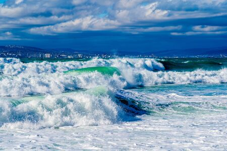 Photo pour Storm waves in white foam rush in rows along the Tsemesskaya Bay. Blue sky and green sea. Dangerous and dramatic. In the background, mountains, multi-storey buildings of the city and port - image libre de droit