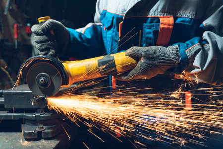 Photo pour Locksmith in special clothes and goggles works in production. Metal processing with angle grinder. Sparks in metalworking. - image libre de droit