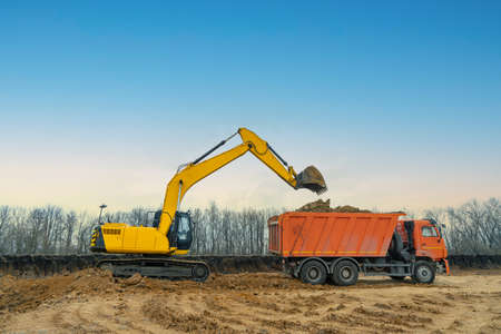 Photo pour A large construction excavator of yellow color on the construction site in a quarry for quarrying. Industrial image - image libre de droit