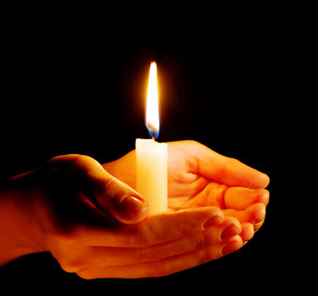 Photo pour Burning of the candle in a hand in darkness - image libre de droit