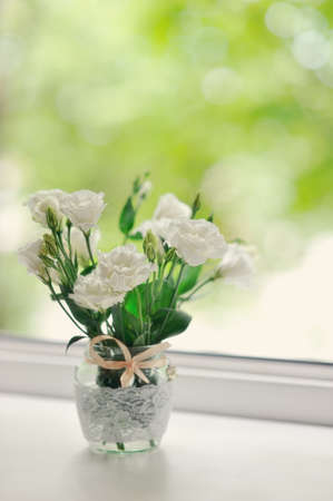 Bouquet of scarlet roses in a pot on a window sill early in
