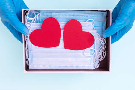 Foto de Hands in blue medical gloves hold an open gift box with protective medical masks and two red heart shapes. Safe gifts concept. Actual gift for Valentine's Day during the coronavirus period - Imagen libre de derechos