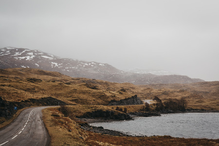 Photo pour Road going through Scottish Highlands near Lochinver on a foggy spring day. - image libre de droit