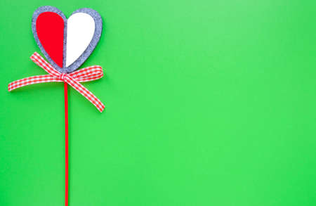 Valentine card on a green background. Heart on a stick.
