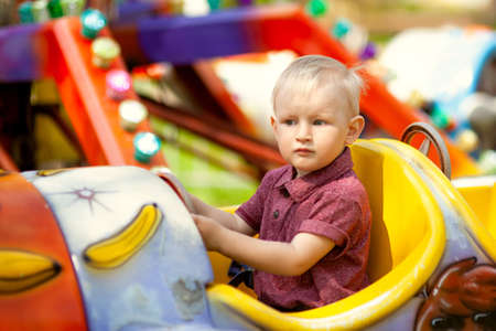 Photo for beautiful blond boy having fun on the amusement rides at the amusement Park - Royalty Free Image