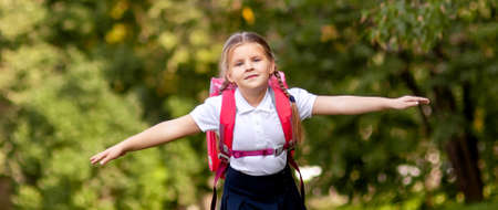 Foto de The little schoolgirl is running with a backpack and laughing. The concept of school, study, education, friendship, childhood. - Imagen libre de derechos