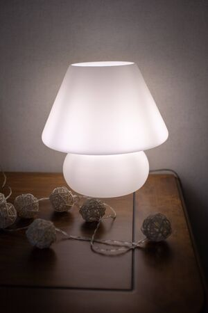 Photo for Classic white lamp on a dark chest of drawers made of dark wood. - Royalty Free Image