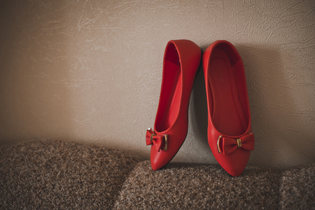 Beautiful red shoes against a wall.