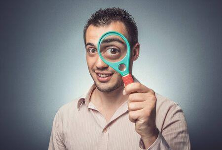 Photo pour Funny man with magnifier looking, big eye, dark gray background. Studio shot - image libre de droit
