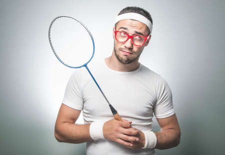 Photo pour Funny sport man with racket think and looking up, isolated on gray background. Facial expression nerd - image libre de droit