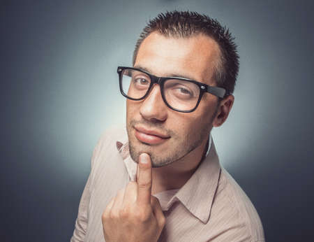 Photo pour Close up of a funny man with eyeglasses. Face expression employee with finger on chin over dark gray background. Studio shot - image libre de droit