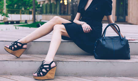 Photo pour Girl sitting on the stairs with a big black super fashionable handbags in a dress and High Wedge Sandals on a warm summer evening. Part of body. Outdoor. - image libre de droit