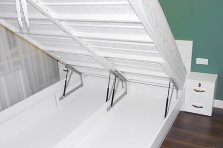 Photo pour A large bed of white oak with a lifting mechanism. Bed with lifting mechanism. Bright bedroom young - image libre de droit