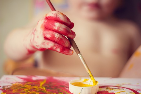 Foto de The boy paints on paper. Red and yellow paint. Children's activities. Children's hobby. Drawing - Imagen libre de derechos