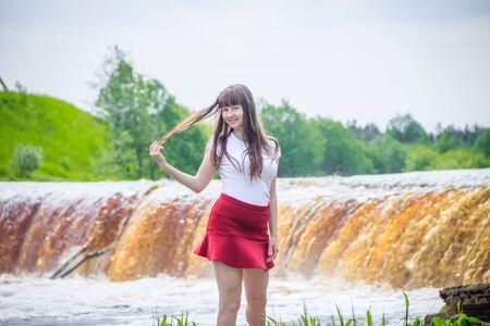 Foto de The girl at the waterfall. Young beautiful girl on a little waterfall. Little waterfall. - Imagen libre de derechos